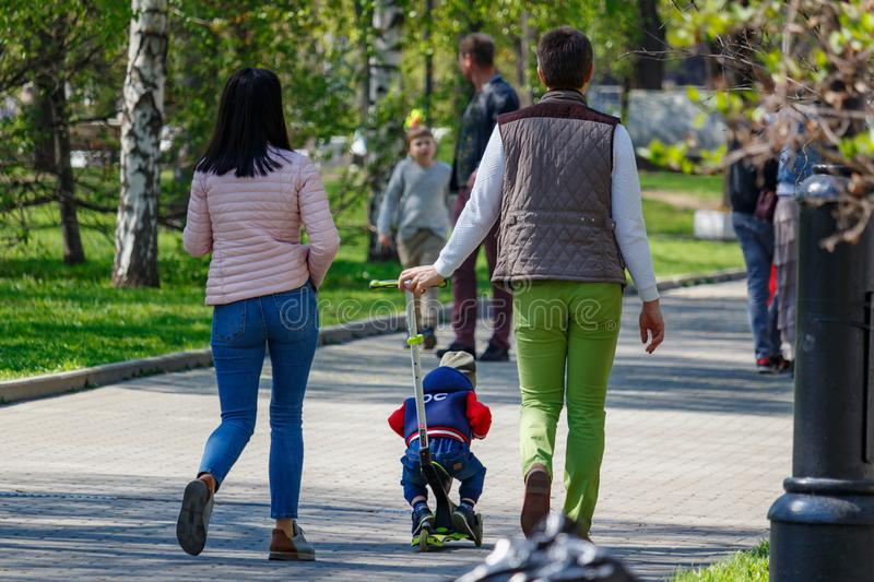 Moscow, Russia - May 01, 2019: Young family with small child walking in the public park in Moscow at sunny morning stock photography