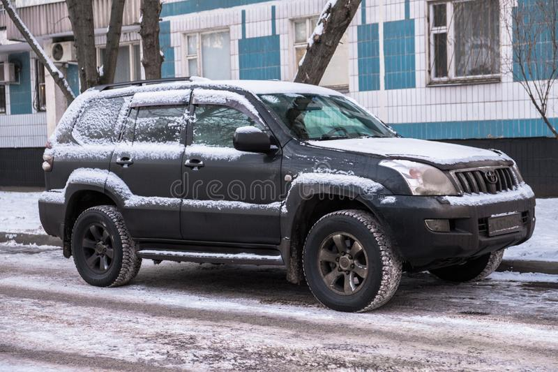 MOSCOW, RUSSIA,NOVEMBER,28.2018:Abandoned snow covered car Toyota Land Cruiser on a big city street.Consequences of snowfall stock photo