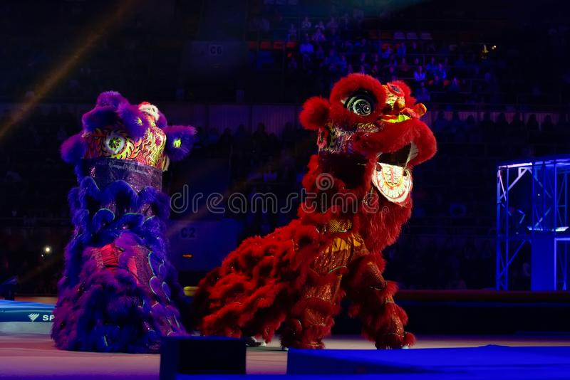 """Blue and Red Dragons. MOSCOW, RUSSIA - NOVEMBER 16-17, 2018: Chinese dragon and gymnasts from China at the Alexey Nemov`s show """"Legends of Sport stock photo"""