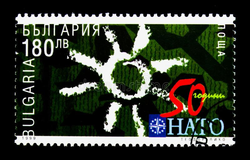 "NATO Emblem, Number. MOSCOW, RUSSIA - NOVEMBER 25, 2017: A stamp printed in Bulgaria shows NATO Emblem, Number ""50"", Sun, 50 Years NATO serie, circa stock image"