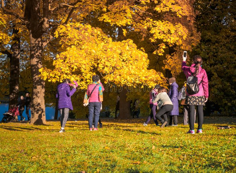 Moscow, Russia - October 11, 2018: Chinese tourists walks autumn park. Asian people take pictures on the background of a stock photo