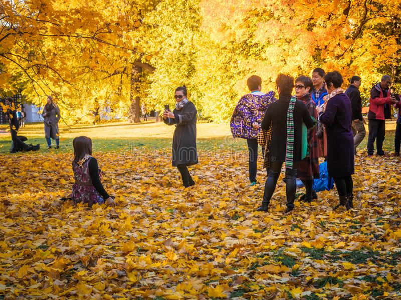 Moscow, Russia - October 11, 2018: Chinese tourists walks autumn park. Asian people take pictures on the background of a royalty free stock photos