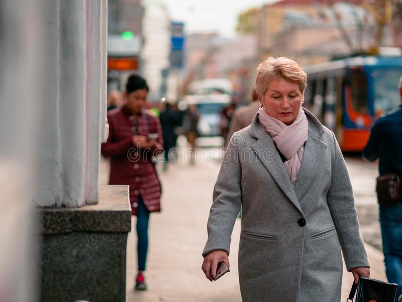 Moscow, Russia - October 19, 2019: Elderly blonde woman in coat holds  smartphone in her hand and walks along the street. The. Phone has become indispensable stock photography
