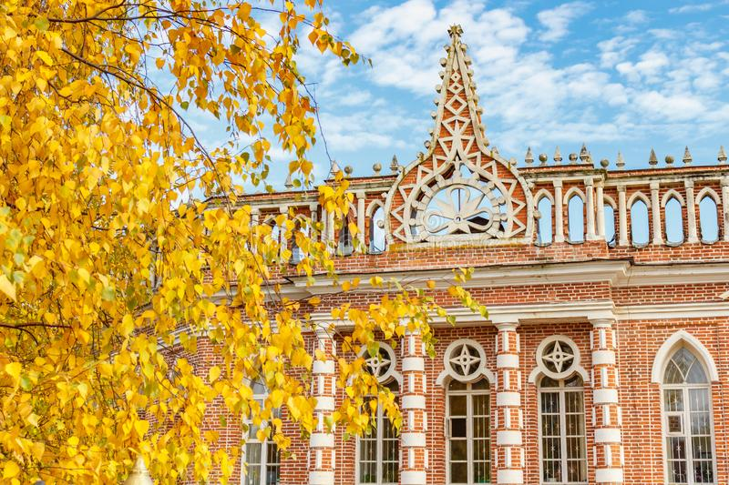 Moscow, Russia - October 16, 2019: Facade of the 2nd Cavalier House building against blue sky and birch branches with yellow. Leaves in sunny autumn day stock photo