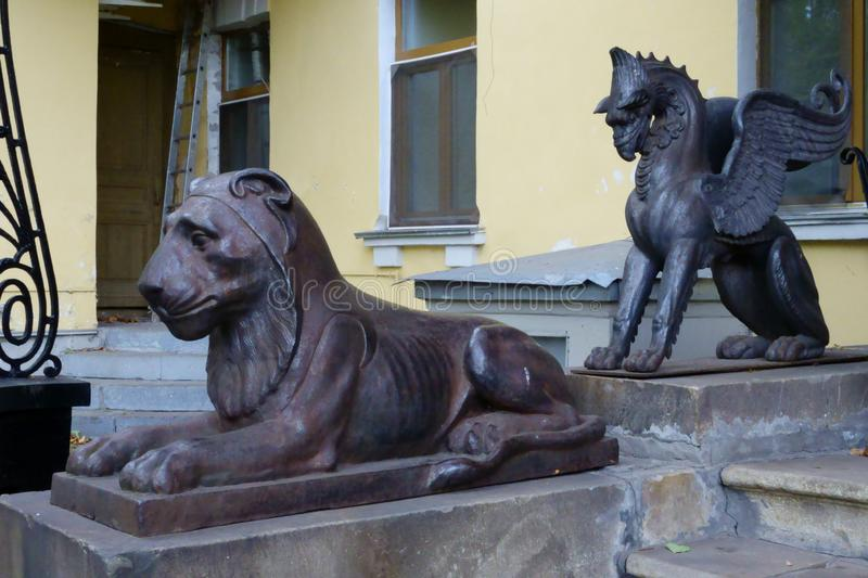 Statues of a cast-iron lion and the fairy-tale griffin royalty free stock photography