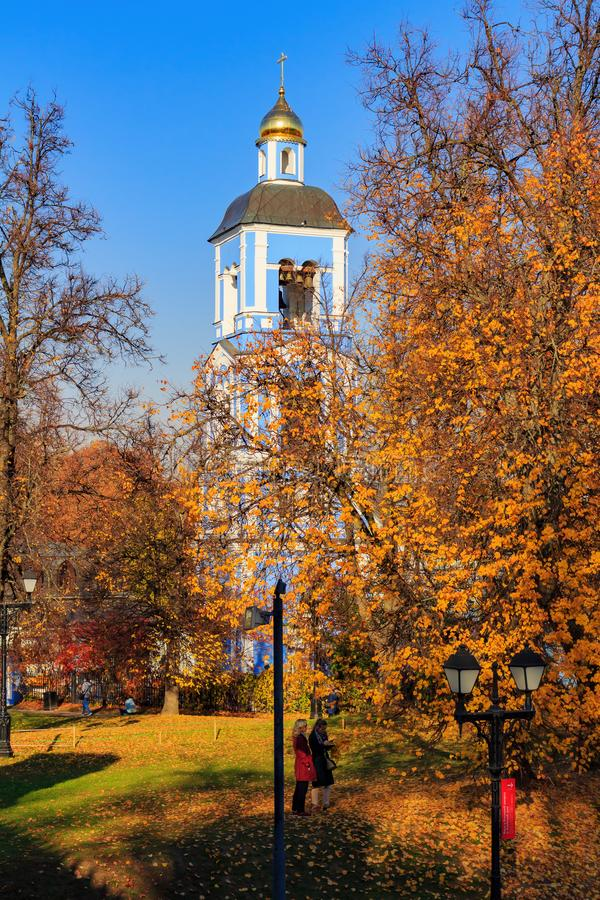 Moscow, Russia - October 17, 2018: People walking on lawn covered with colored leaves against Church of the icon of the mother of. God in Tsaritsyno park in royalty free stock photo