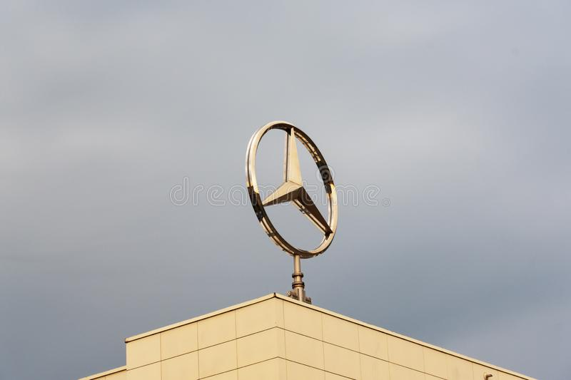 MOSCOW, RUSSIA OCTOBER 4, 2019: Rotating Mercedes Benz logo on a building opposite a cloudy sky stock photo