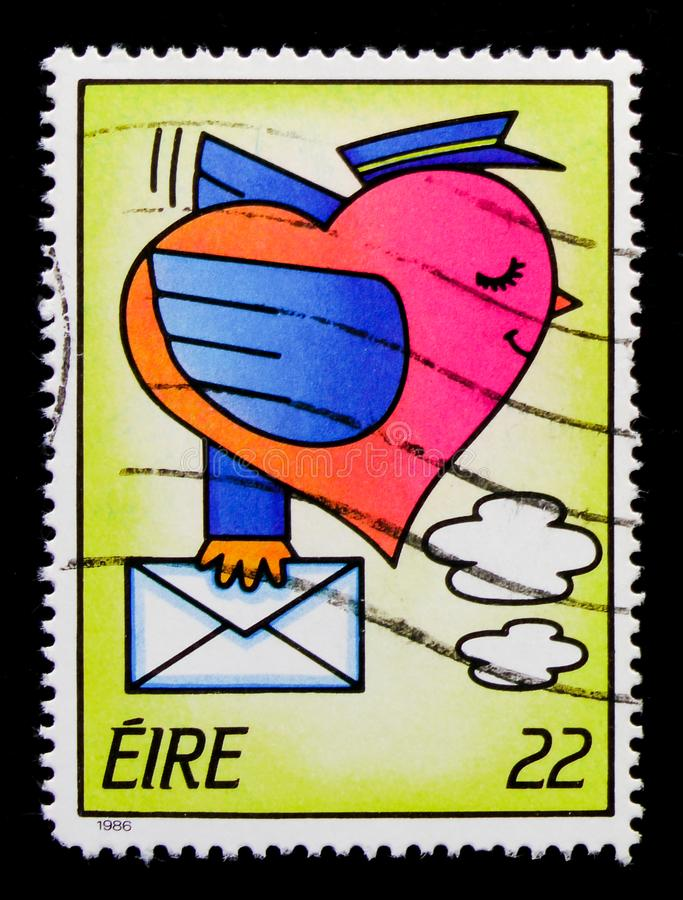 Stylised Love Bird with Letter, Greetings Stamps 1986 serie, circa 1986. MOSCOW, RUSSIA - OCTOBER 1, 2017: A stamp printed in Ireland shows Stylised Love Bird royalty free stock image