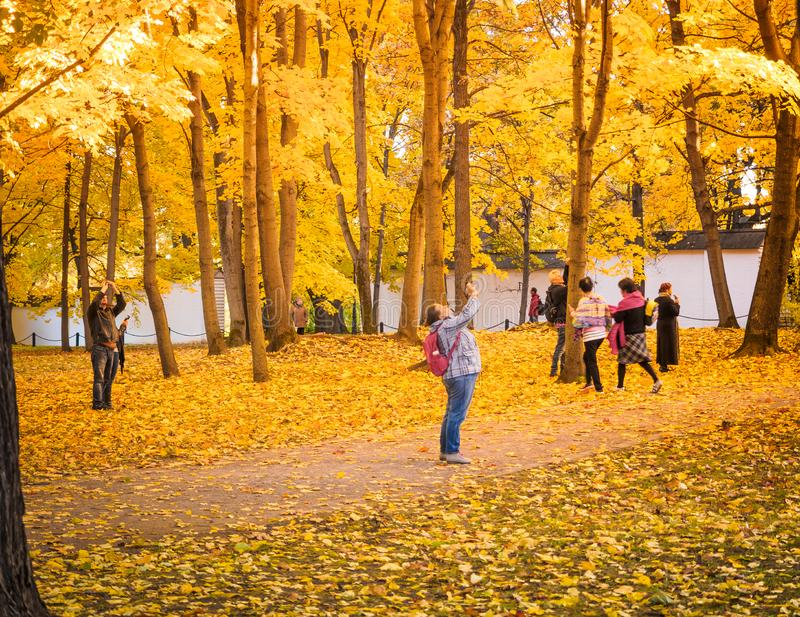 Moscow, Russia - October 11, 2018: Tourists walks autumn park. People take pictures on the background of a beautiful stock photos