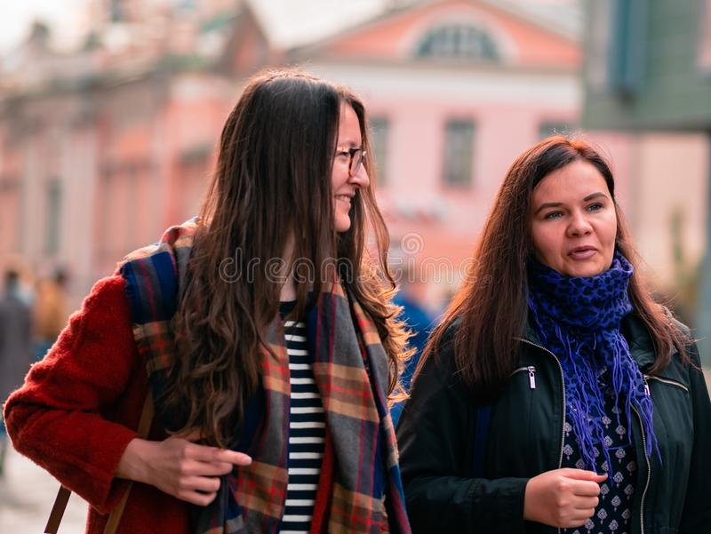 Moscow, Russia - October 19, 2019: Two girlfriends walk along the street and have a fun conversation. Young women are walking in stock image