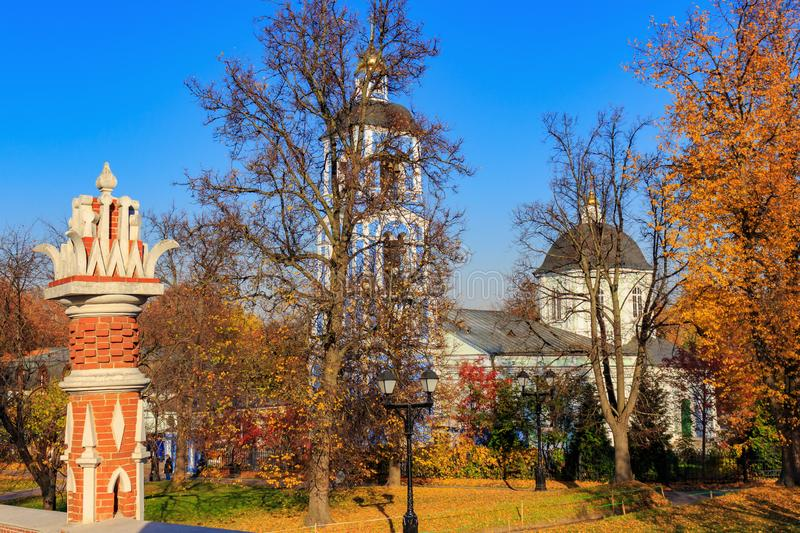 Moscow, Russia - October 17, 2018: View of Church of the icon of the mother of God on a background of trees and lawn covered with. Colored leaves in Tsaritsyno stock photography