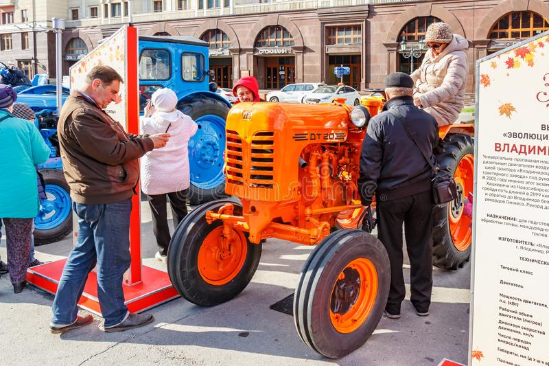 Moscow, Russia - October 08, 2019: Visitors of exhibition of agricultural machinery on Revolution Square in Moscow near restored. Orange soviet wheel tractor stock photos