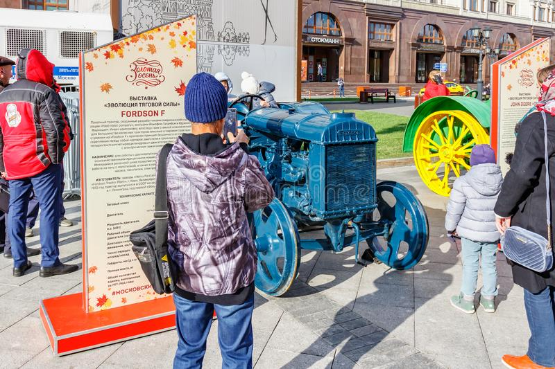 Moscow, Russia - October 08, 2019: Visitors of exhibition of agricultural machinery on Revolution Square in Moscow takes a photo. Of restored american wheel royalty free stock photography