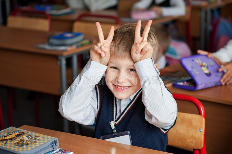 Moscow, Russia, September 2012. Change in primary school. The boy in school uniform smiles and builds faces. Bright emotions royalty free stock photo