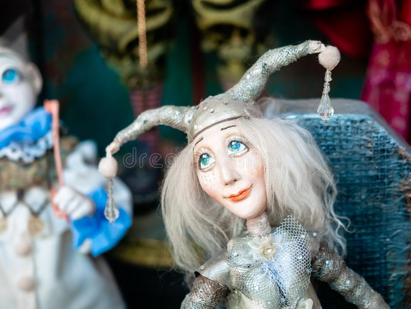 Dolls depicting fairytale heroes in a window of a Moscow Puppet Theater. The figure of a Jester or harlequin with blue eyes in hat royalty free stock photo