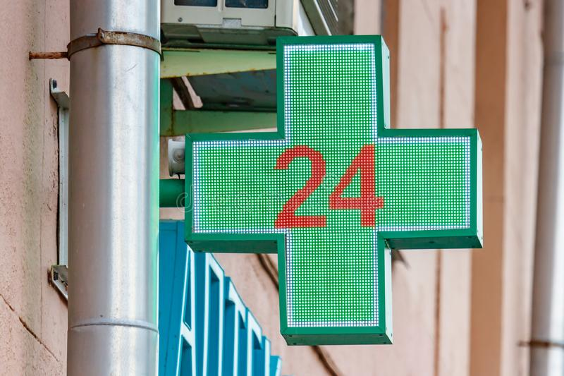 Moscow, Russia - September 13, 2019: LED green cross with numeric 24 above entrance to the pharmacy. Symbol of 24-hour pharmacy stock images
