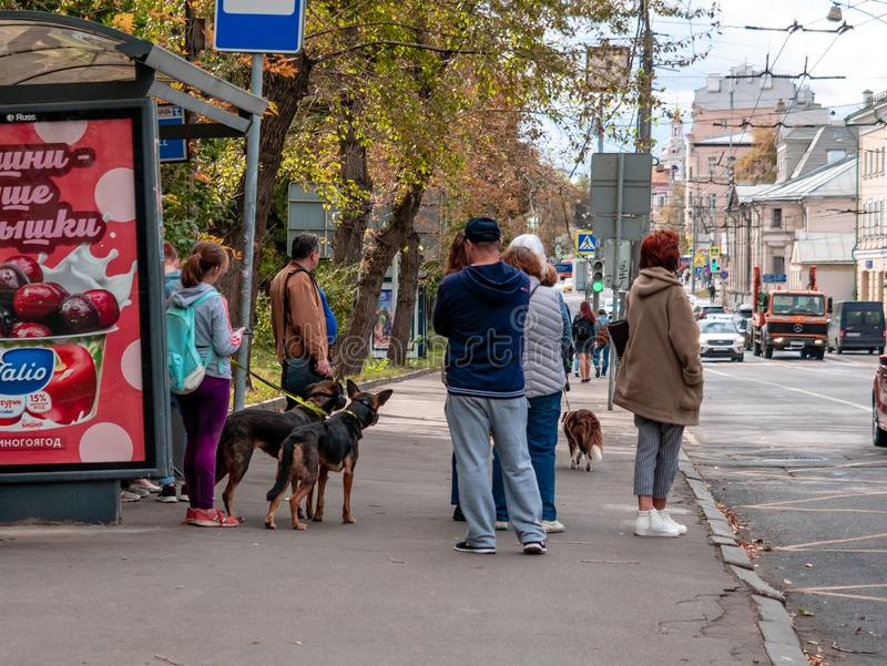 Moscow, Russia - September 14, 2019: People stand at a public transport stop. Passengers waiting for a bus on a city street. A stock photography