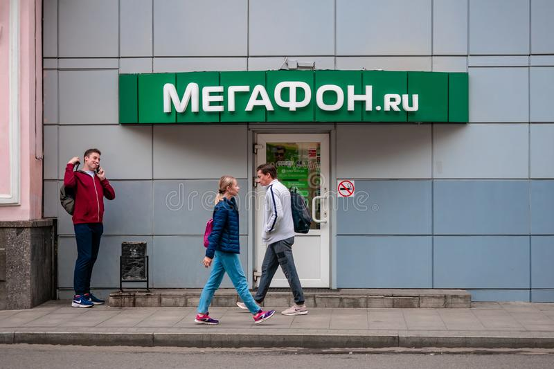 People walk past MegaFon showroom. MegaFon, previously known as North-West GSM is second largest mobile phone operator and third l royalty free stock photos