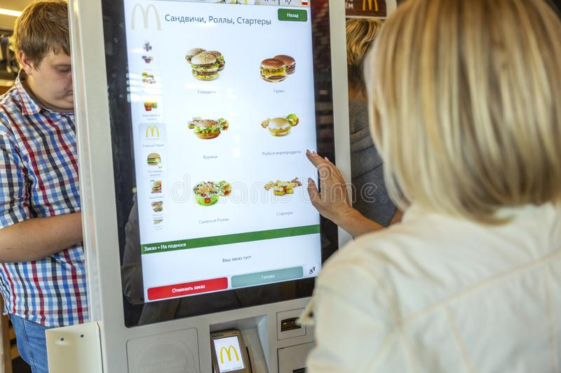 Moscow, Russia, 08/11/2019: A woman chooses food at McDonald`s in the electronic menu. Horizontal stock images