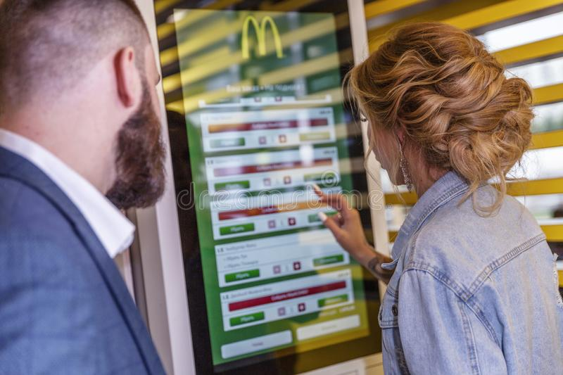 Moscow, Russia, 08/02/2019: Young beautiful woman in McDonald`s chooses food on an electronic board. Hprizontal stock images