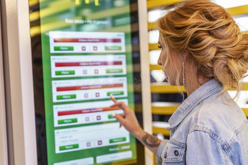 Moscow, Russia, 08/02/2019: Young beautiful woman in McDonald`s chooses food on an electronic board. Horizontal stock photography