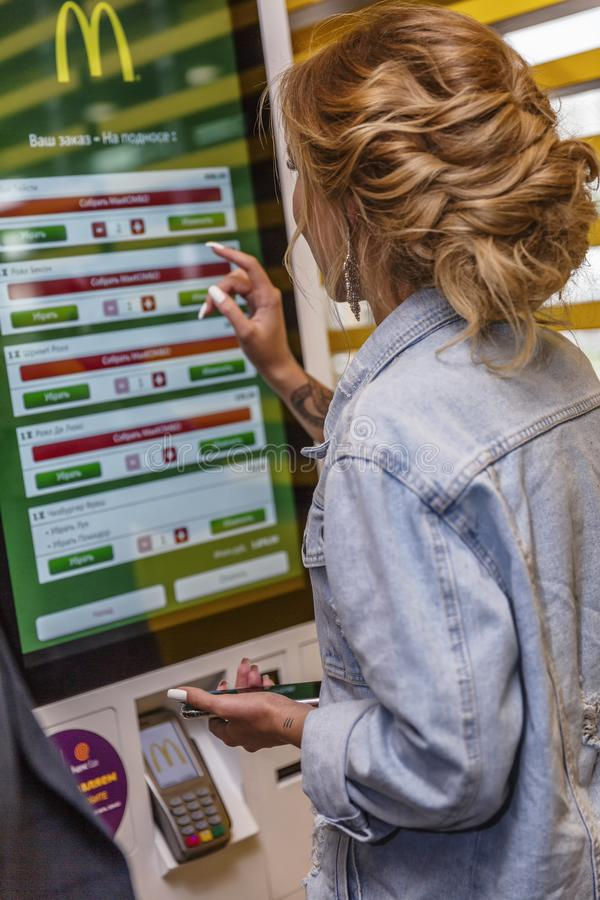 Moscow, Russia, 08/02/2019: Young beautiful woman in McDonald`s chooses food on an electronic board. Vertical royalty free stock photography