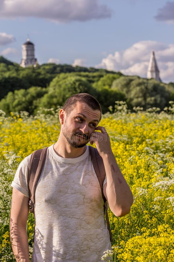A young man standing on the blooming field on background of an old churches. 2019.06.01, Moscow, Russia. A young man standing on the blooming field on royalty free stock photography
