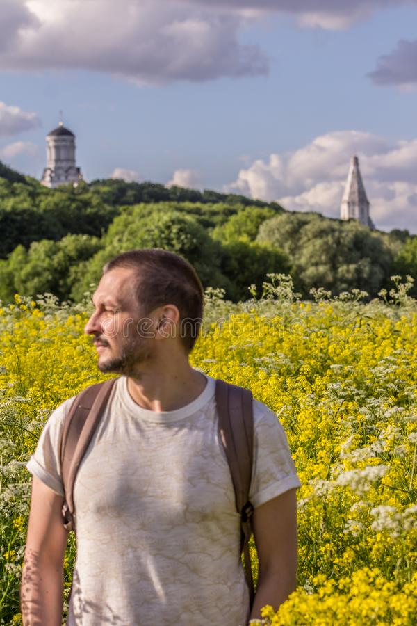 A young man standing on the blooming field on background of an old churches. 2019.06.01, Moscow, Russia. A young man standing on the blooming field on royalty free stock photos