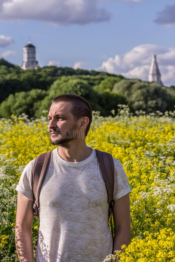 A young man standing on the blooming field on background of an old churches. 2019.06.01, Moscow, Russia. A young man standing on the blooming field on royalty free stock images
