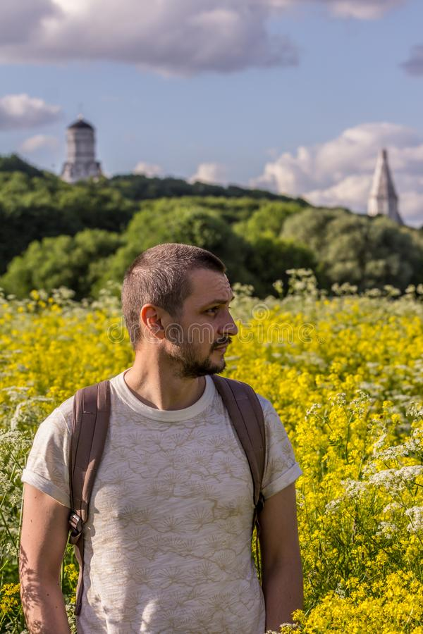 A young man standing on the blooming field on background of an old churches. 2019.06.01, Moscow, Russia. A young man standing on the blooming field on stock image