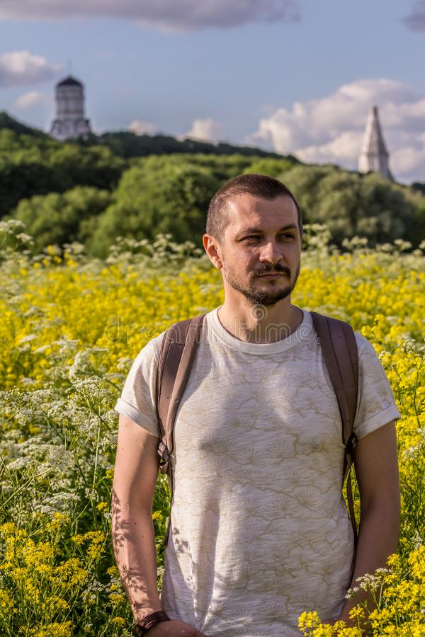 A young man standing on the blooming field on background of an old churches. 2019.06.01, Moscow, Russia. A young man standing on the blooming field on royalty free stock photo