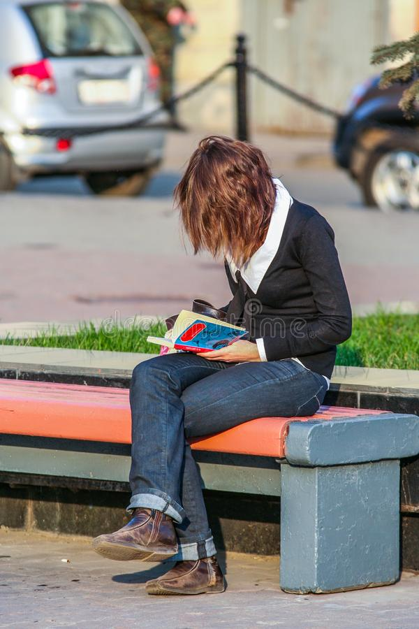 A young woman reading a book and sitting on the bench. royalty free stock photography