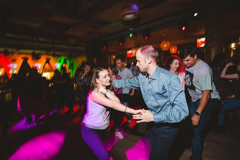 MOSCOW, RUSSIAN FEDERATION - OCTOBER 13, 2018: A middle-aged couple, a man and a woman, dance salsa among a crowd of dancing peopl. E in a nightclub Tiki bar royalty free stock photo