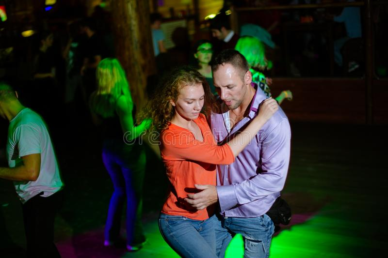 MOSCOW, RUSSIAN FEDERATION - OCTOBER 13, 2018: A middle-aged couple, a man and a woman, dance salsa among a crowd of dancing peopl. E in a nightclub Tiki bar royalty free stock photos