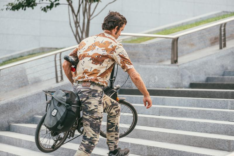 MOSCOW, RUSSIN FEDERATION - JULY 28, 2017: Side view of a camouflaged male cyclist with bicycle under his arm walking up stock image