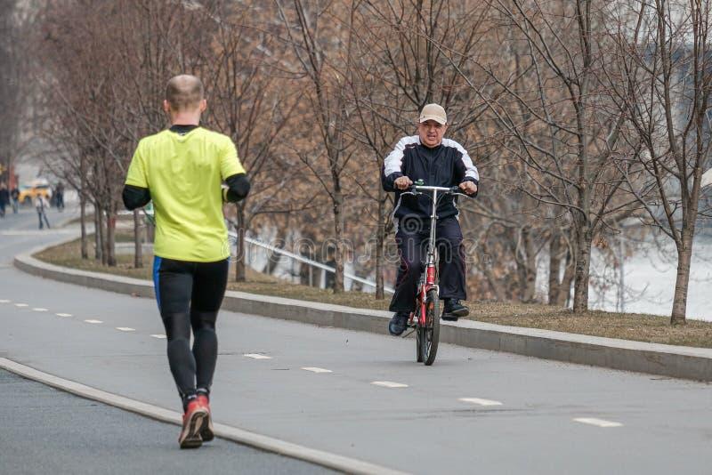 moscow Ryssland E En man på en cykel går att möta en man som begår en körning Sportfritid i Moskva arkivbilder