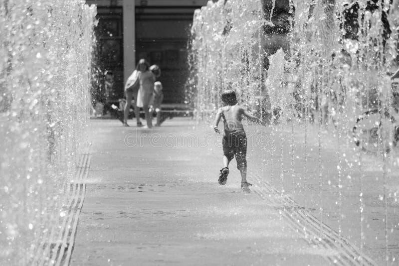 moscow Ryssland Juni 19, 2019 Barn som badar i en uppfriskande sprej av stadsspringbrunnen på en varm sommardag arkivbilder
