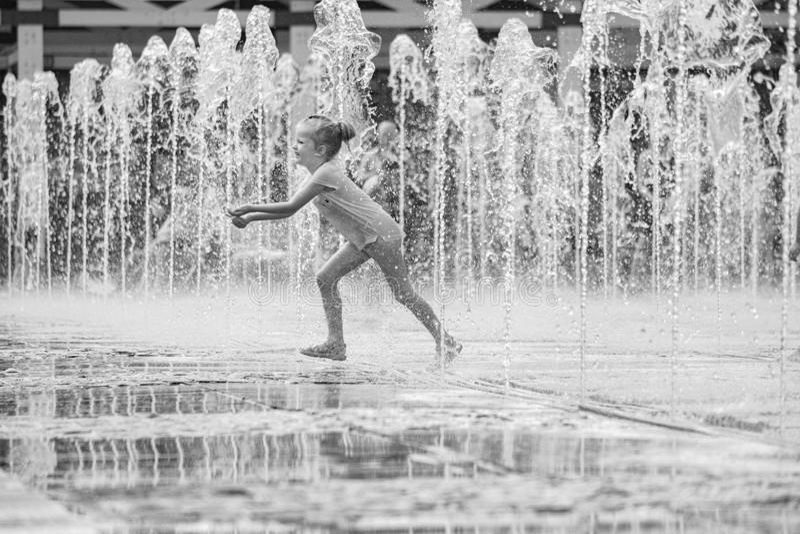 moscow Ryssland Juni 19, 2019 Barn som badar i en uppfriskande sprej av stadsspringbrunnen på en varm sommardag royaltyfri fotografi