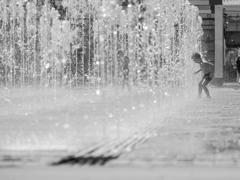 moscow Ryssland Juni 19, 2019 Barn som badar i en uppfriskande sprej av stadsspringbrunnen på en varm sommardag royaltyfria bilder