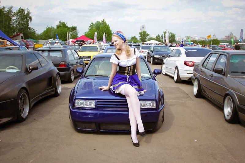 moscow Ryssland - Maj 20, 2019: En ung flicka i en nationell tysk dräkt står framme av en stämd tysk bil i blått royaltyfria bilder