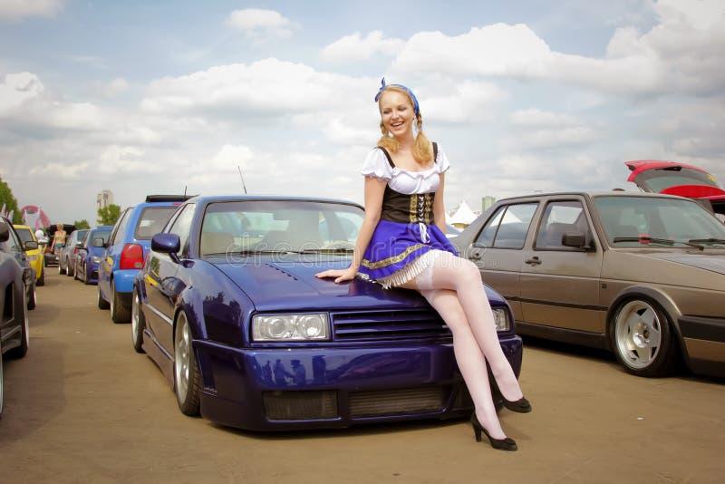 moscow Ryssland - Maj 20, 2019: En ung flicka i en nationell tysk dr?kt st?r framme av en st?md tysk bil i bl?tt arkivfoton