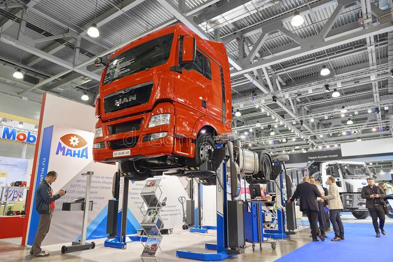 MOSCOW, SEP, 5, 2017: Maintenance equipment, repair tools and special devices for trucks. Red MAN truck lifted on special car lift. Elevator hoist on Commercial stock image