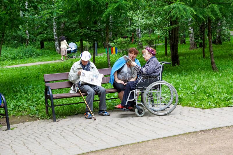 Pensioners and disabled people in a wheelchair read newspapers stock photo