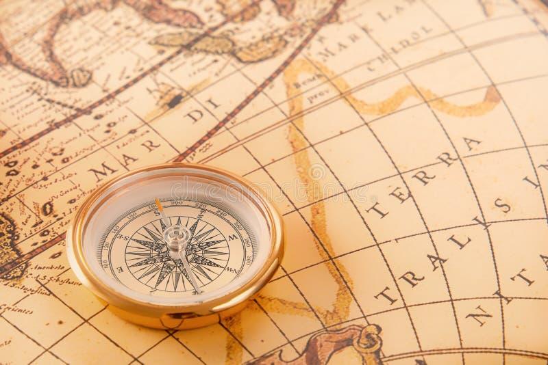 Mosiężny kompas odpoczywa na starej rocznik mapie zdjęcia royalty free