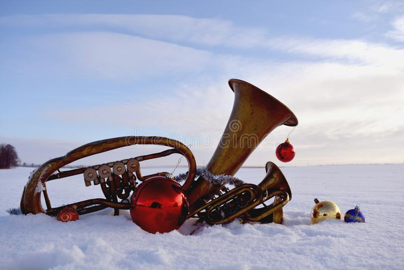 Mosiężny muzykalny wiatrowy instrument na śnieżnych i Bożenarodzeniowych baubles fotografia stock