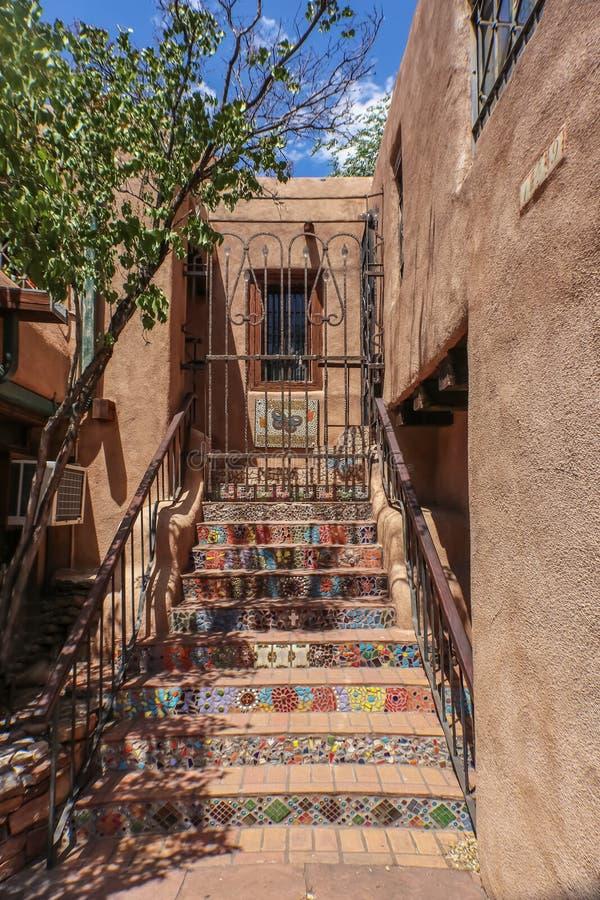 Mosiac跨步导致对第二个故事入口和一个锁着的铁门在多孔黏土大厦 免版税库存照片
