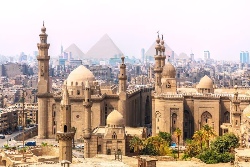 Moskén-Madrassa av Sultan Hassan och pyramiderna i bakgrunden, Kairo, Egypten fotografering för bildbyråer