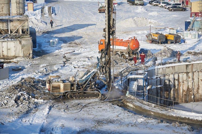 MOSKAU, FEB 01, 2018: Winteransicht über schmutzige schwere Baugeräte, Fahrzeuge und Arbeitskräfte bei der Arbeit Bohrende Operat lizenzfreies stockbild