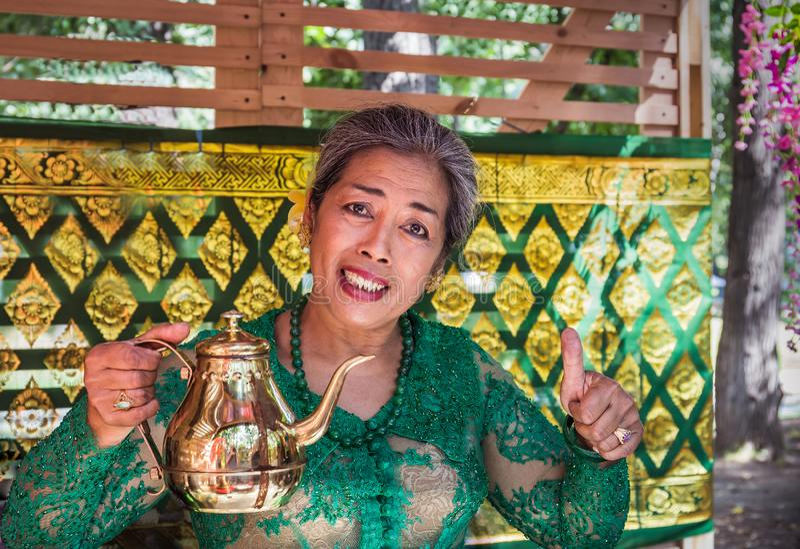 Moskau, Park auf Krasnaya Presnya, am 5. August 2018: eine ältere Frau von Indonesien in einem grünen Kleid lächelt und bietet Te lizenzfreies stockfoto