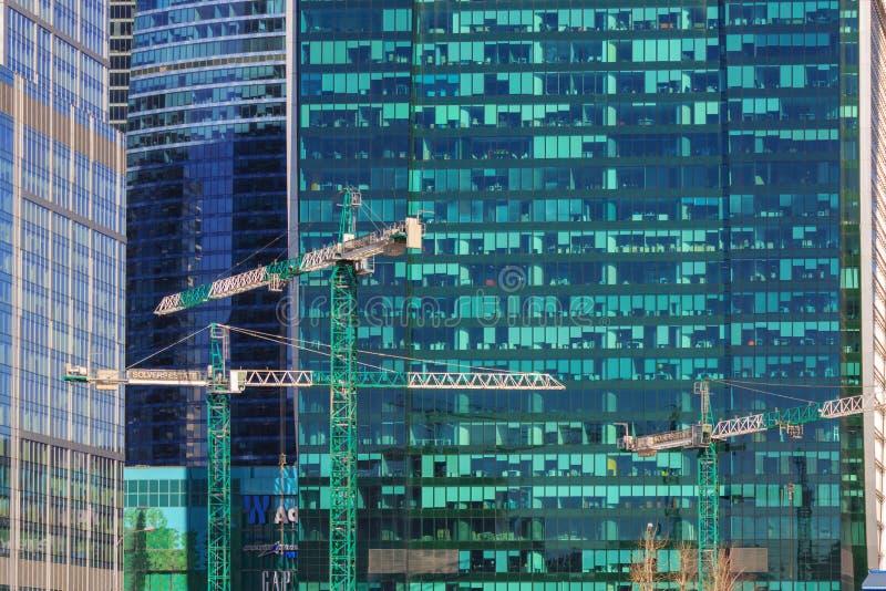 Moskau, Russland - 14. April 2018: Baukräne auf dem Hintergrund von Glasfassaden von Wolkenkratzern am sonnigen Tag stockfoto